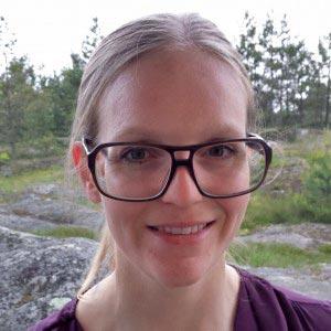 Porträtt på en kvinna med glasögon som står utomhus.